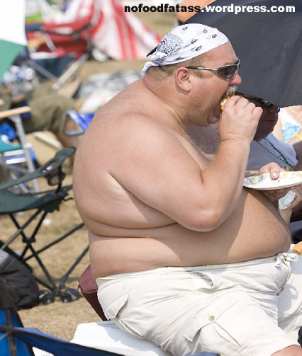 Fat shirtless guy eating cheesburger